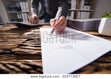 Close-up Of A Businessperson's Hand Using Calculator While Signing Document On Wooden Desk