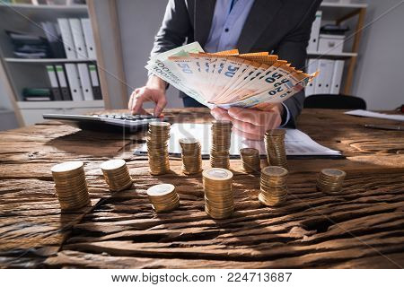 Businessperson Calculating Euro Banknotes With Stacked Golden Coins On Desk