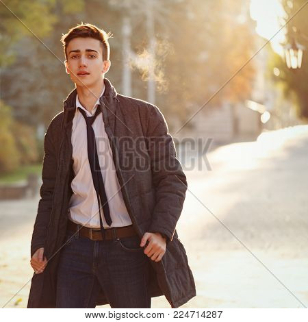 Young stylish teenager guy with a weakened tie is walking along the alley. Street youth fashion. Backlight of the setting sun
