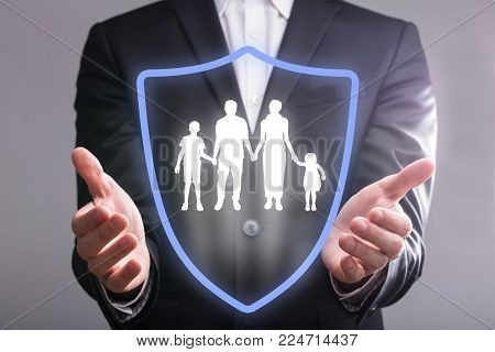 Close-up Of A Businessperson's Hand With Shield Protecting Family