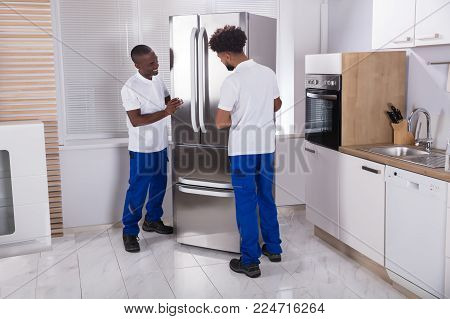 Two Male Movers In Uniform Fixing The Freezer In The Kitchen At Home