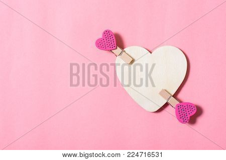 White heart with pink clothes pegs (heart shape) on pink background, Valentine concept