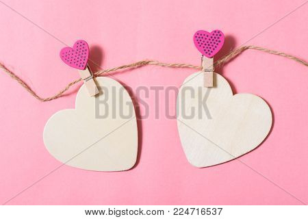 Two white hearts with pink clothes pegs (heart shape) on pink background, Valentine concept