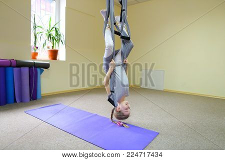 Beautiful girl of American appearance performs acrobatic elements in air, child concentrates and calmly holds on acrobatic ropes. Room nice warm lighting, walls delicate yellow and large windows, on windowsill pots with flowers, under wall  folded rugs