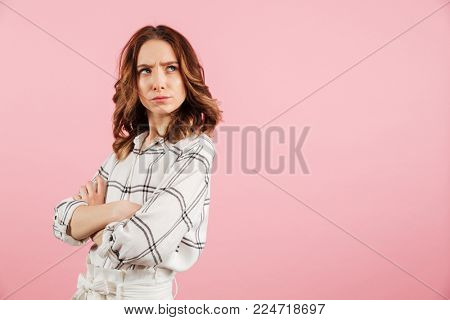 Portrait of an upset young woman standing with arms folded and looking away at copy space isolated over pink background
