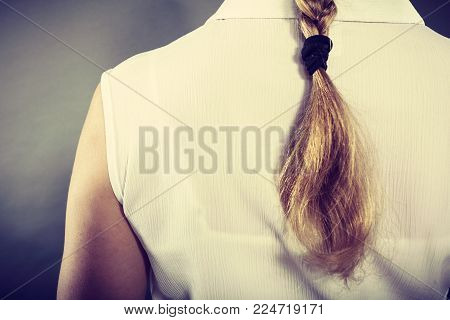 Hairstyle and hairdo concept. Back view of blonde woman with long elegant braid. Girl with beautiful coiffure.