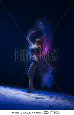 Graceful girl in top and shorts dancing in a cloud of blue and pink dust full-length profile shot in dark room