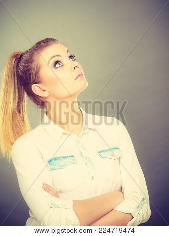 Negative emotion, feelings attitude. Angry grumpy young woman looking very displeased standing with arms folded, serious face expression on dark