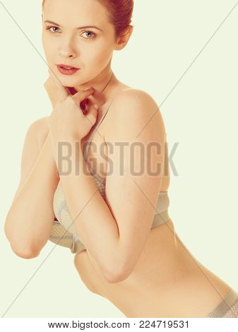 Femininity, underclothes concept. Attractive slim red head woman in romantic grey matching underwear. Studio shot on white background