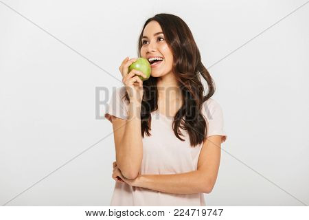 Portrait of a cheerful young asian woman eating green apple isolated over white background