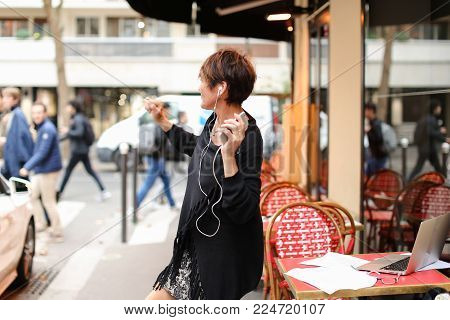 middle-aged woman tourist standing near Italian cafe and listen music in smartphone by earphones. Pretty lady with short haircut have good mood and dancing to music. Female shaking hands swinging from side to side, sing along. Concept of listening music