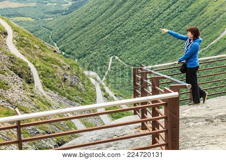 Travel concept. Tourist woman looking at Trolls Path Trollstigen or Trollstigveien winding scenic mountain road from viewing point, Norway Europe