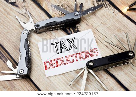 Conceptual hand writing text caption inspiration showing Tax Deductions. Business concept for Finance Incoming Tax Money Deduction written on old wooden background with pocket knife with space