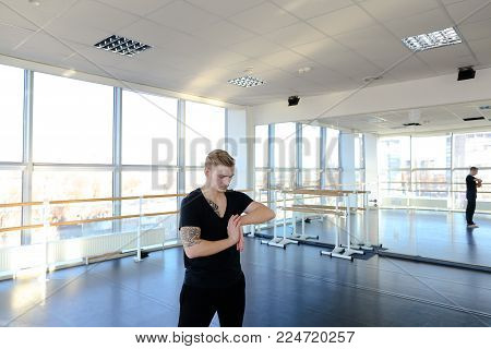 Programmer in sportswear do gymnastics to avoid problems with back, guy has sedentary work and go to sport gym to keep fit. Tattooed boy sitting on floor in position of string sloping. Concept of well-equipped hall, sport clothes or individual training.