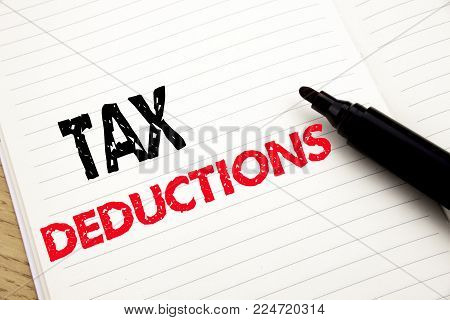 Tax Deductions. Business concept for Finance Incoming Tax Money Deduction written on notebook with space on book background with marker pen