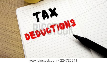 Handwritten text caption showing Tax Deductions. Business concept writing for Finance Incoming Tax Money Deduction writte notebook with copy space on book background with marker pen