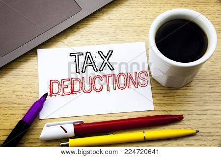 Handwritten text caption showing Tax Deductions. Business concept writing for Finance Incoming Tax Money Deduction written on notebook book on wooden background in the Office with laptop coffee
