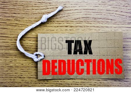Tax Deductions. Business concept for online saleFinance Incoming Tax Money Deduction written on price tag paper with copy space on wooden vintage background