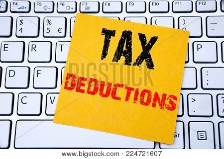 Tax Deductions. Business concept for Finance Incoming Tax Money Deduction written on sticky note paper on white keyboard background.