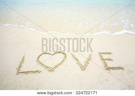 Happy Valentines Day, Love Lettering On The Beach With Wave And Sunlight. Heart Shape Message Writte