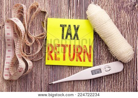 Tax Return. Business fitness health concept for Accounting Money Return written on wood wooden background with bandage and thermometer