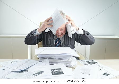 Angry senior businessman covering his head with documents while sitting at office desk overwhelmed by work, portrait shot