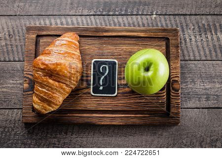 Healthy and unhealthy food. Green Apple vs Croissant. Diet Concept