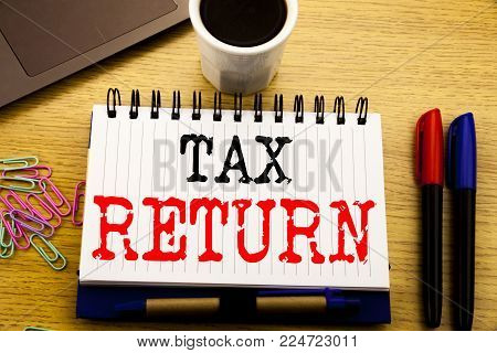 Hand writing text caption showing Tax Return. Business concept for Accounting Money Return written on notebook on the wooden background in the Office with laptop coffee
