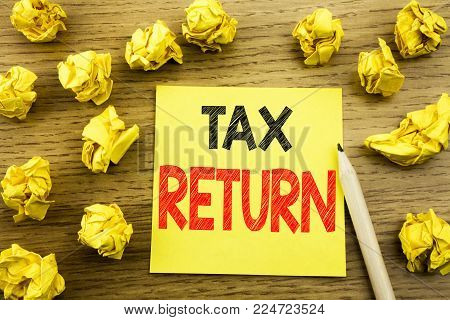 Word, writing Tax Return. Business concept for Accounting Money Return written on sticky note paper on wooden background. Folded yellow papers on the background