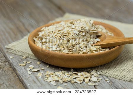 Oat Flakes Or Oatmeal In Wooden Bowl On Rustic Wood Table. Rolled Oat Is Clean Food For Health Lover