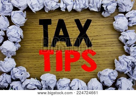 Handwriting Announcement text showing Tax Tips. Business concept for Taxpayer Assistance Refund Reimbursement written on wooden wood background with on old background with folded paper balls