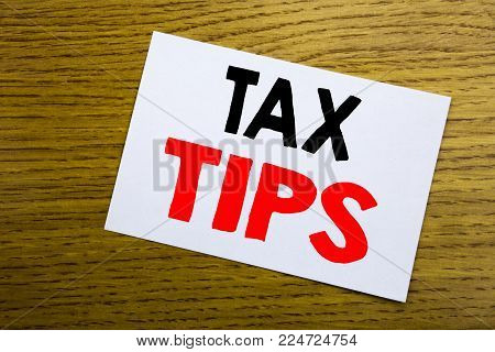 Tax Tips. Business concept for Taxpayer Assistance Refund Reimbursement written on sticky note, wooden background with copy space.