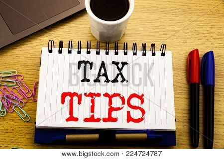 Hand writing text caption showing Tax Tips. Business concept for Taxpayer Assistance Refund Reimbursement written on notebook on the wooden background in the Office with laptop coffee
