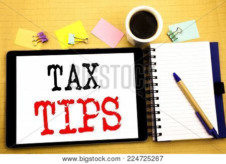 Tax Tips. Business concept for Taxpayer Assistance Refund Reimbursement Written on tablet, wooden background with sticky note and pen
