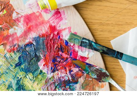 fine art, creativity and artistic tools concept - close up of palette knife or painting spatula and paintbrush from top