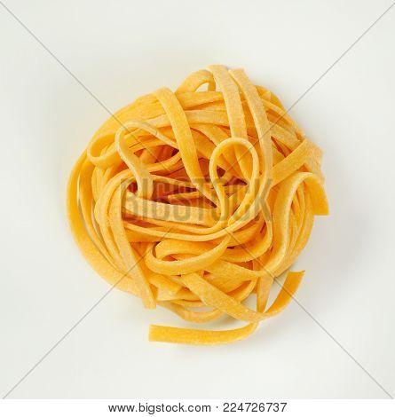 bundle of dried ribbon pasta on white background