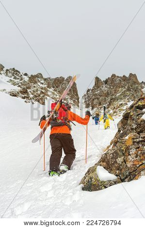 Extreme skiers and snowboarders climb to the top along the couloir between the rocks before the freeride backcountry descent. The concept of a group extreme winter sport. Freeride culture and backcountry wild skiing