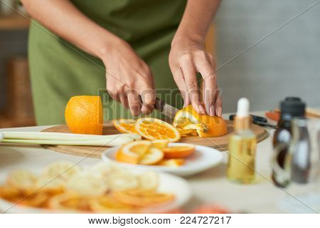 Close-up image of woman cutting orange to add it into soap she is making