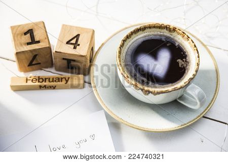 The heart is reflected in a cup of coffee on the table next to the wooden calendar. Valentine's Day Concept