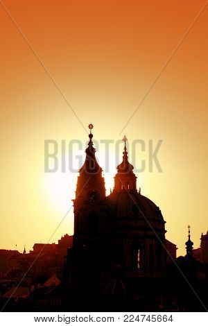 Sunset backlit silhouettes of Saint Nicholas Church and roofs of cityscape skyline of lesser old town in Prague, Czech Republic