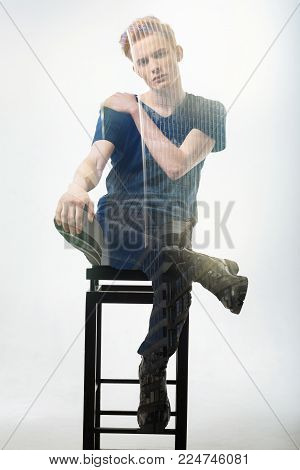 Serious handsome redhead man sitting in the room on the chair holding leg on the other and left hand on right shoulder and looking straight.