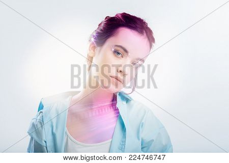 Cute stylish serious girl standing in the empty room looking straight tilting head left.