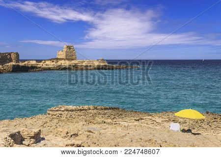 Summertime.Realx on beach: a place in the sun. The most beautiful coast of Apulia: Roca Vecchia, ITALY (Lecce).Typical seascape of Salento: cliff and ruins of ancient coastal watchtower.
