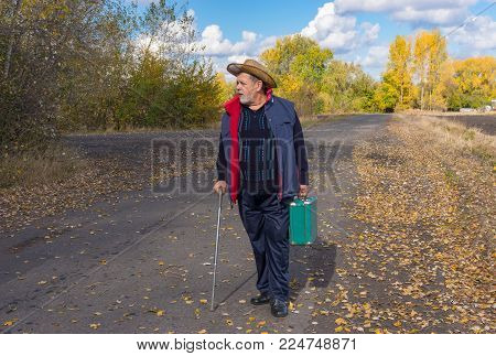 Senior man with walking stick standing on a country road and holing an old green suitcase