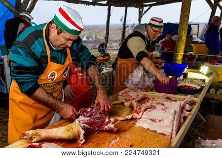 Hecha, Ukraine - January 27, 2018: Hungarian butchers cut pork to prepare national dishes during the 12th International Festival of Butchers.
