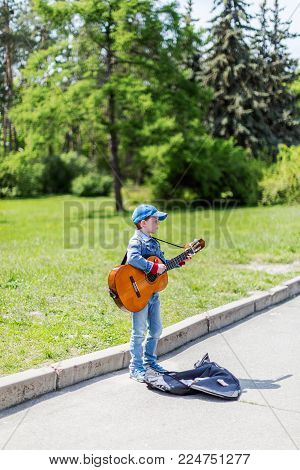 KYIV, UKRAINE May 01, 2016. Boy playing on acoustic guitar outdoors. Little street musician