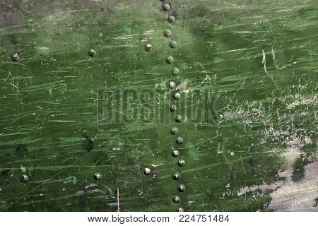 Surface of the aluminum sheet in rivets, shabby green paint and numerous scratches