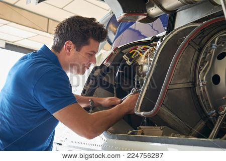 Male Aero Engineer Working On Helicopter In Hangar