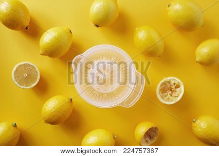 Making lemonade with fresh lemons and lemon squeezer against a yellow background.