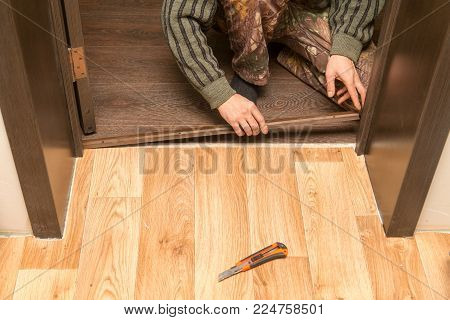A man is making a threshold on the floor .